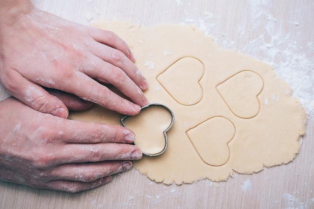 Meisje maakt koekjes in de vorm van een hart in de keuken, close-up. verras uw dierbaren op valentijnsdag, moederdag of vaderdag. feestelijke culinaire achtergrond, met liefde.