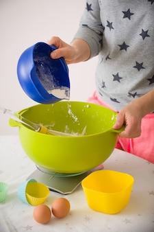 Meisje maakt muffindeeg door meel, suikereieren en andere ingrediënten uit kleurrijke kommen te mengen