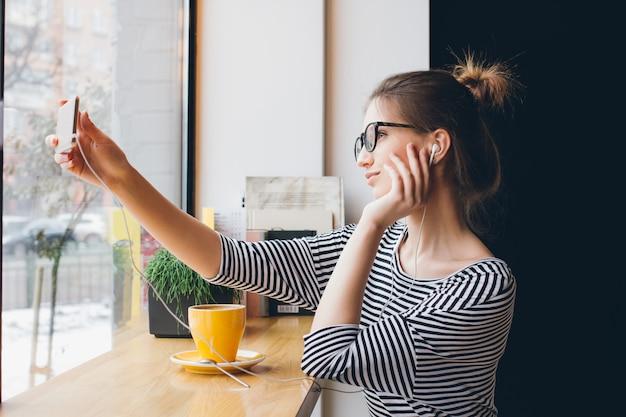 Meisje maakt selfie op smartphone in coffeeshop
