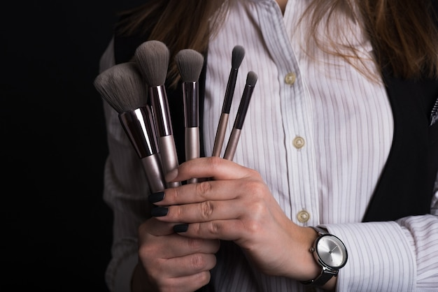 Meisje make-up artiest houdt borstels voor visage