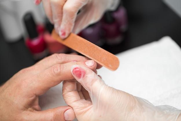Meisje manicure doen manicure voor man in de schoonheidssalon