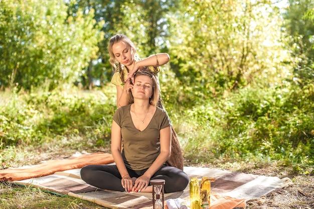 Meisje masseuse demonstreert verfrissende massagemethoden in het bos.