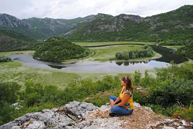 Meisje mediteren op de rivier crnojevica