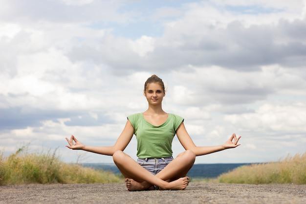 Meisje mediteren op de stoep. jong mooi meisje dat yoga in aard doet. actief type rust