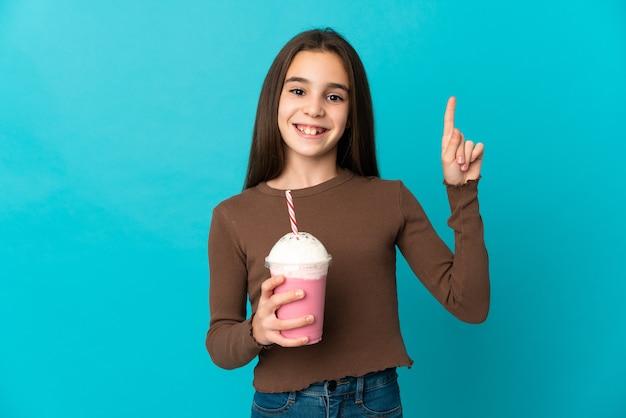 Meisje met aardbeimilkshake die op blauwe achtergrond wordt geïsoleerd die een geweldig idee benadrukt