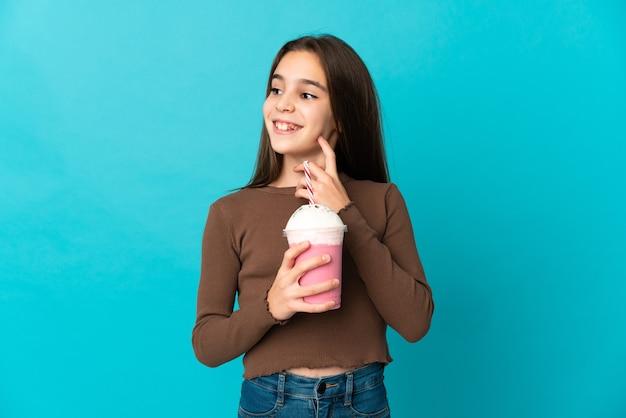 Meisje met aardbeimilkshake die op blauwe achtergrond wordt geïsoleerd die een idee denkt terwijl het opzoeken