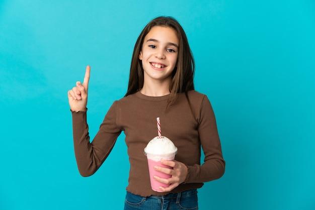 Meisje met aardbeimilkshake die op blauwe achtergrond wordt geïsoleerd die en een vinger in teken van het beste opheft