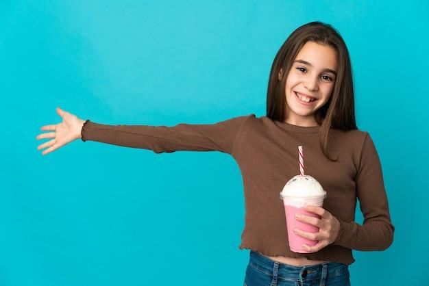 Meisje met aardbeimilkshake die op blauwe achtergrond wordt geïsoleerd die handen uitbreidt naar de kant om uit te nodigen om te komen
