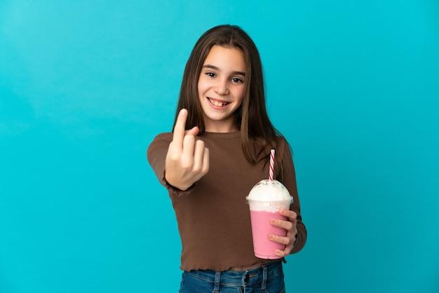 Meisje met aardbeimilkshake die op blauwe achtergrond wordt geïsoleerd die komend gebaar doet