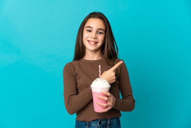 Meisje met aardbeimilkshake die op blauwe achtergrond wordt geïsoleerd die naar de kant wijst om een product te presenteren