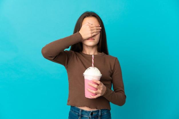 Meisje met aardbeimilkshake die op blauwe achtergrond wordt geïsoleerd die ogen behandelt door handen. ik wil niets zien