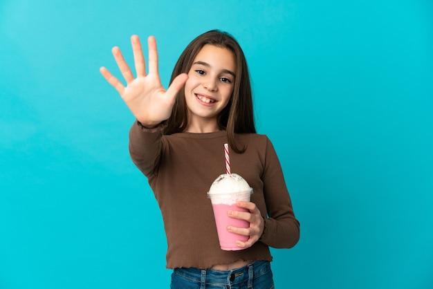 Meisje met aardbeimilkshake die op blauwe achtergrond wordt geïsoleerd die vijf met vingers telt