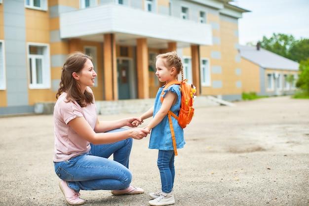 Meisje met aktentassen dichtbij de school.