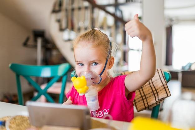 Meisje met allergisch astma gebruikend inhalator en tonend ok.