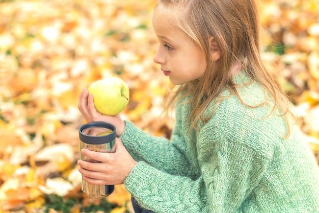 Meisje met appel en drankje in herfst park