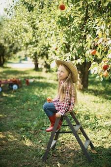 Meisje met appel in de appelboomgaard. mooi meisje dat organische appel in de boomgaard eet.