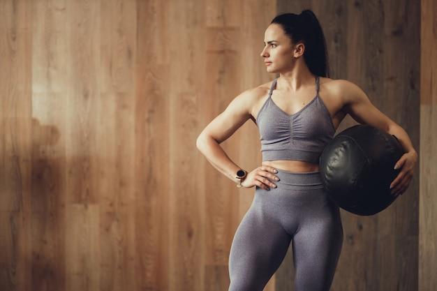 Meisje met atletische lichaamsbouw poseren met fitball op de achtergrond van de houten muur van de sportschool voor crossfit