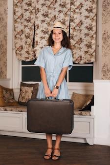 Meisje met bagage die op een reis wacht.