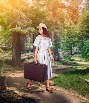 Meisje met bagage wandelen in het bos.