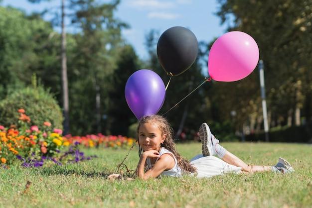 Meisje met ballons die in gras liggen