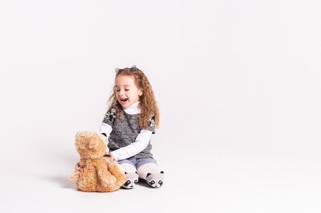 Meisje met beer die zich op wit bevindt