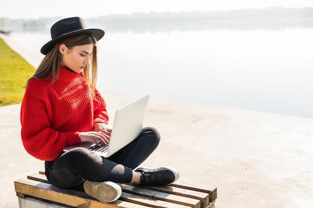 Meisje met behulp van een laptop op een bankje