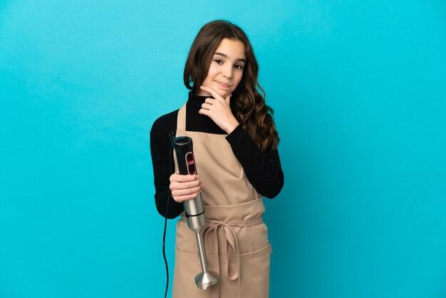 Meisje met behulp van handmixer geïsoleerd op blauwe achtergrond denken