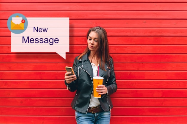 Meisje met behulp van mobiele telefoon, leest een inkomend bericht, met een drankje in haar hand