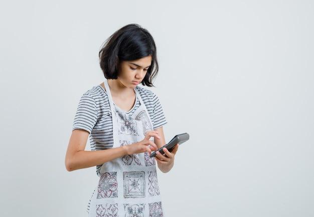 Meisje met behulp van rekenmachine in t-shirt, schort en bezig op zoek