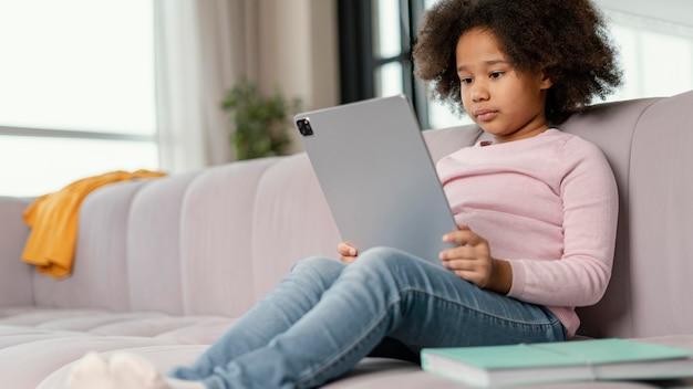 Meisje met behulp van tablet thuis