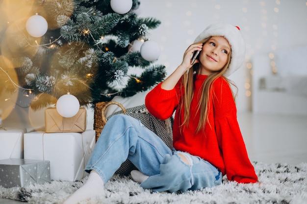 Meisje met behulp van telefoon door kerstboom op kerstmis