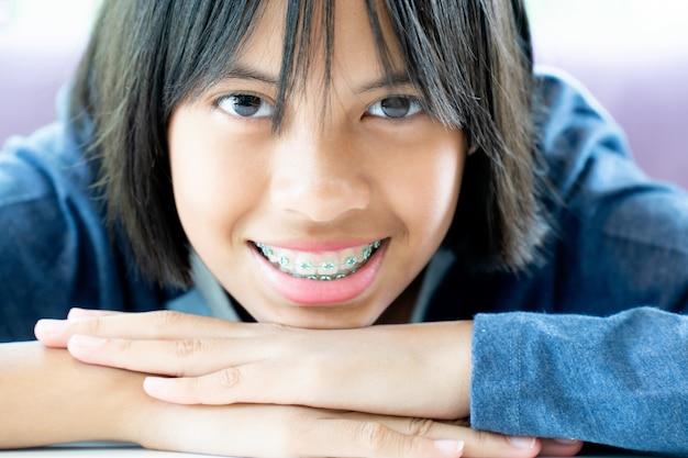 Meisje met beugels tanden glimlachen en gelukkig
