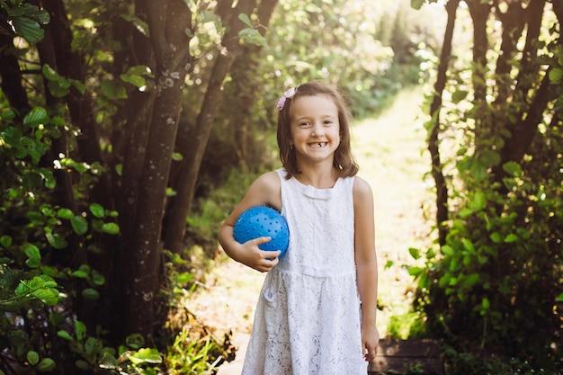 Meisje met blauwe bal staat in de stralen van de zon in het bos