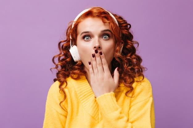 Meisje met blauwe ogen in witte koptelefoon bedekt haar mond met hand in verrassing