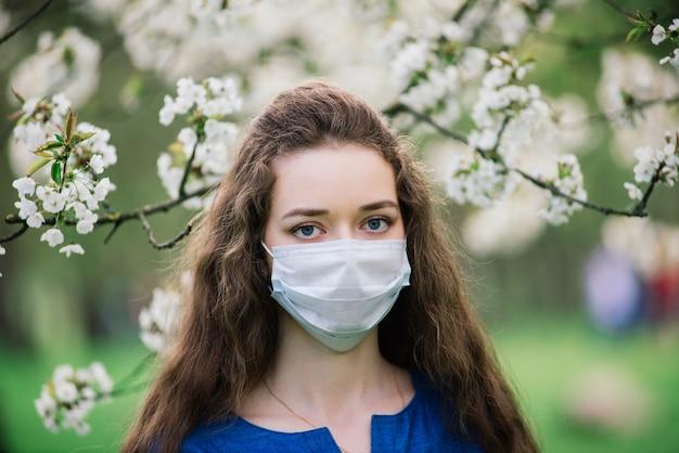 Meisje met blauwe ogen met een medisch masker in het park