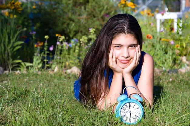 Meisje met blauwe wekker in de zomer