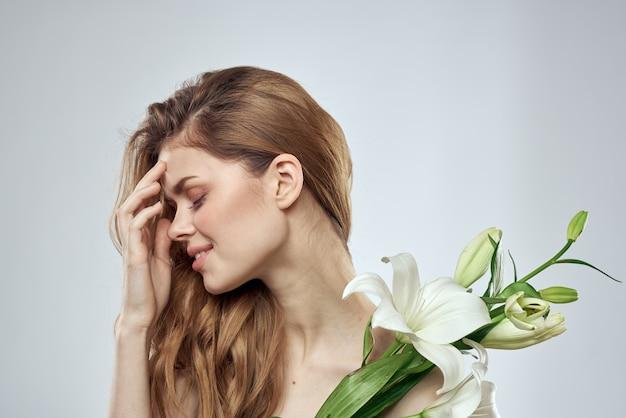 Meisje met bloemen bijgesneden weergave portret close-up lente blote schouders heldere huid make up