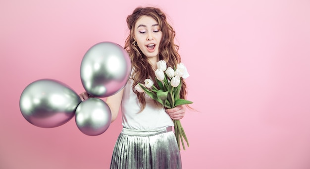 Meisje met bloemen en ballen op een gekleurde achtergrond