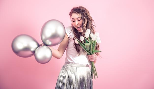 Meisje met bloemen en ballen op een gekleurde muur