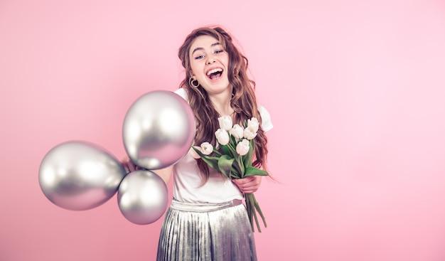 Meisje met bloemen en ballonnen op een gekleurde muur