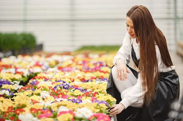 Meisje met bloemen in een serre. tuinman in een schort. verzorging van bloemen.