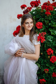 Meisje met bloemen in handen, jonge mooie bruid in witte jurk met bruidsboeket, boeket bruid van rozencrème spray, rozenstruik, roze paars memory lane, violet eustoma, eucalyptus