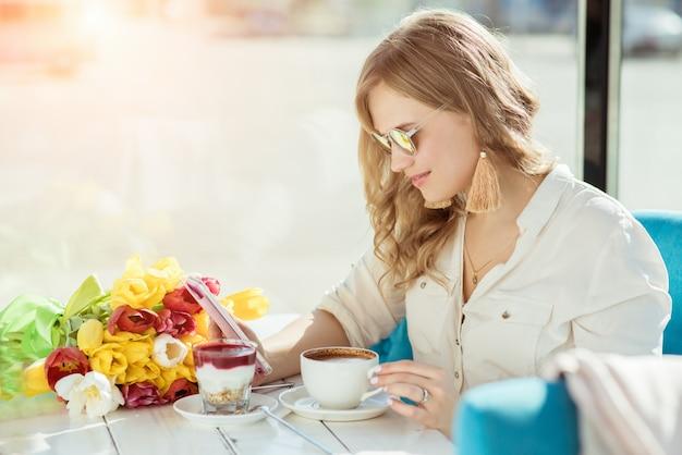 Meisje met bloemen, koffie, yoghurt en telefoon in een café