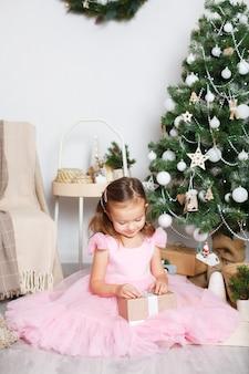 Meisje met blond haar in een elegante roze jurk opent vrolijk een geschenkdoos bij de kerstboom scand