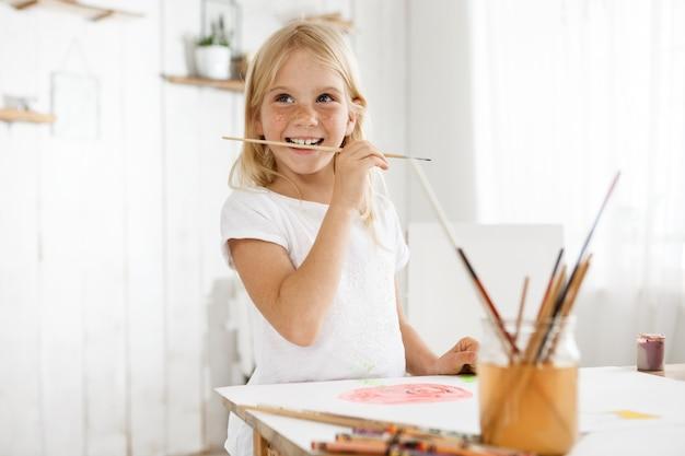 Meisje met blonde haren en sproeten genieten van kunst met wit t-shirt. vrouwelijk kind gevangen door een creatieve impuls bijtende borstel. kinderen, kunst en positieve emoties.