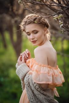 Meisje met blonde haren in een lichte jurk in een bloeiende tuin. concept van vrouwelijke lente mode. meisje in een mooie jurk en gebreide trui geniet van de zonsondergang in een bloeiende peertuin
