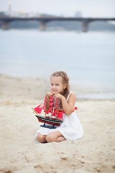 Meisje met blonde haren in witte jurk bedrijf schip met dieprode zeilen. kind zit aan kust, heeft een zeilboot speelgoed in zijn handen.