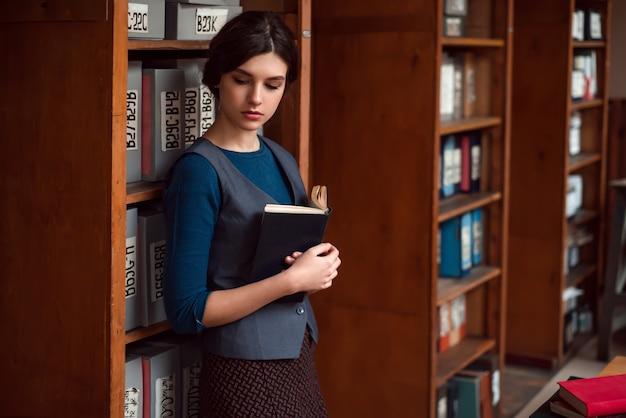Meisje met boek in handen bij de schoolbibliotheek.