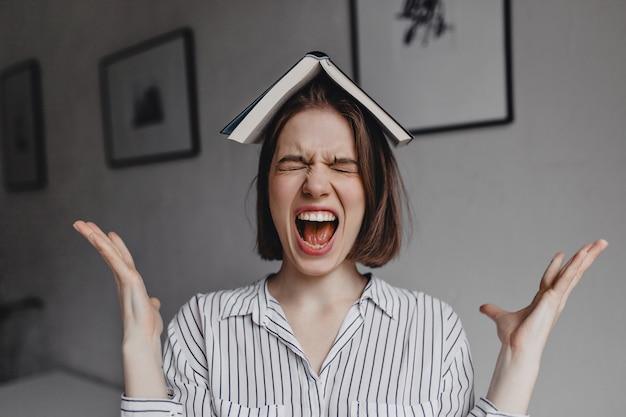 Meisje met boek op haar hoofd schreeuwt heftig. portret van emotionele donkerharige vrouw in witte blouse in kantoor.