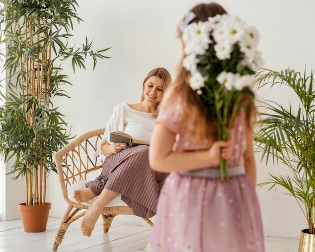 Meisje met boeket van lentebloemen als een geschenk voor haar moeder
